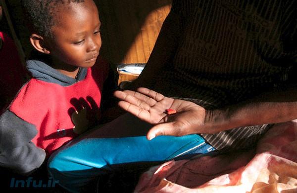 ایتبلنگ گاوسودیوه، مبتلا به ایدز، داروهای پیشگیرانهاش را به فرزند خود نشان میدهد. آنها ساکن حومه گابورون، پایتخت بوتسوانا هستند؛ و هرچند که والدین هر دو به ایدز مبتلا شدهاند، اما هیچکدام از پنج فرزندشان به این بیماری مبتلا نیست / رویترز.