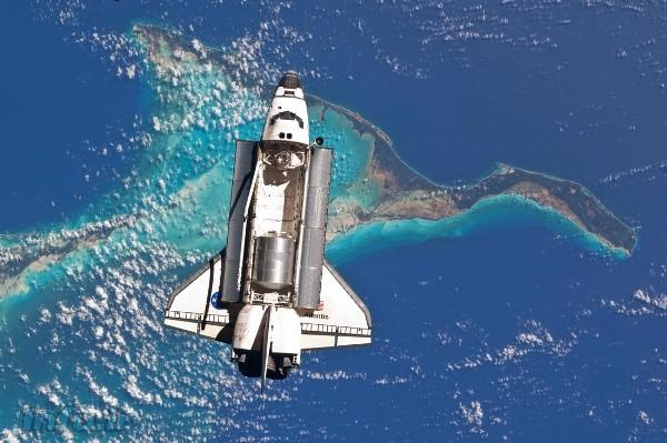 آتلانتیس، بر فراز سواحل باهاما از دریچه دوربین ران گاران. اتاقک لجستیکی چندمنظوره رافائلو در پایین، و گلوگاه اتصال آتلانتیس به ایستگاه هم در بالای محفظه بار آن به چشم میخورد.