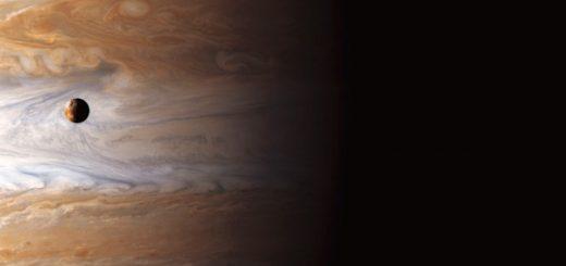 قمر آتشفشانی «یو» در برابر بخشی از سیاره مشتری و طوفانهای گسترده آن؛ در نور مرئی، از دید کاوشگر کاسینی / ناسا