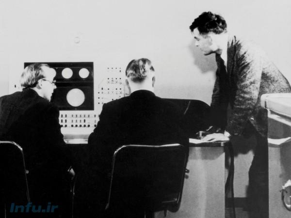 آلن تورینگ (ایستاده) و همکارانش حین کار بر روی کامپیوتر Ferranti Mark 1 در دانشگاه منچستر. مربوط به سال ۱۹۵۱.