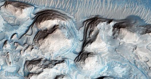 لایهبندیهای رسوبی ناحیهای از دشت Arrabia Terra، از دید ماهواره تجسّسی مریخ. این دشت از جمله مناطقی است که تیم رودریگز احتمال حضور آبرفتهای سیلابی ناشی از سونامیهای کهن مریخ را در آن میدهند / NASA / دانشگاه آریزونا