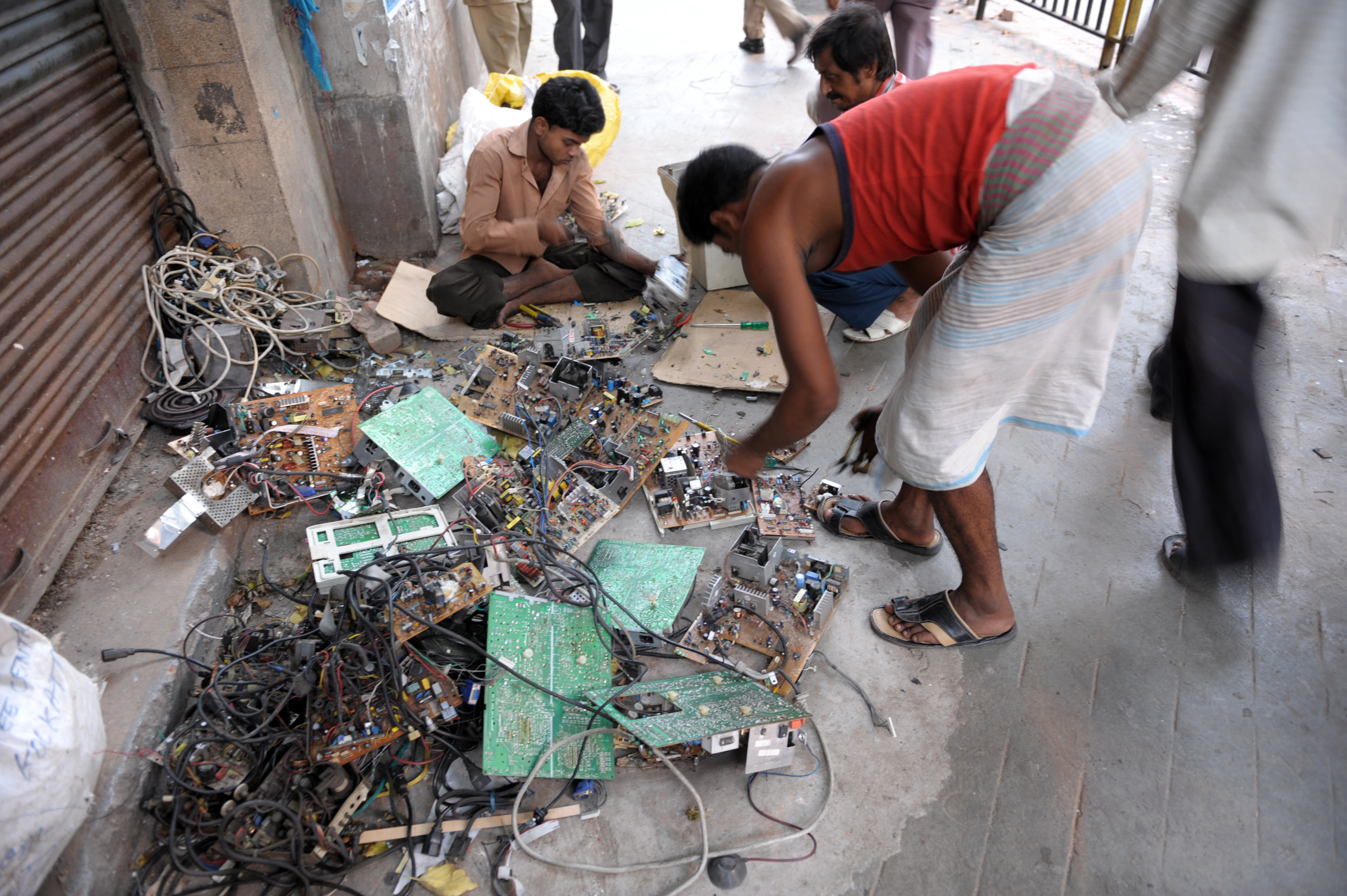 Indian youths dismantle reusable parts from electronic waste on a pavement of Kolkata on June 5, 2009, while the nation celebrates the World Environment Day. India is likely to generate as much as 800,000 tonnes of electronic waste by 2012, and there's only one government - registered recycling firm, Indian news paper The Hindu reports. AFP PHOTO/Deshakalyan CHOWDHURY / AFP PHOTO / DESHAKALYAN CHOWDHURY