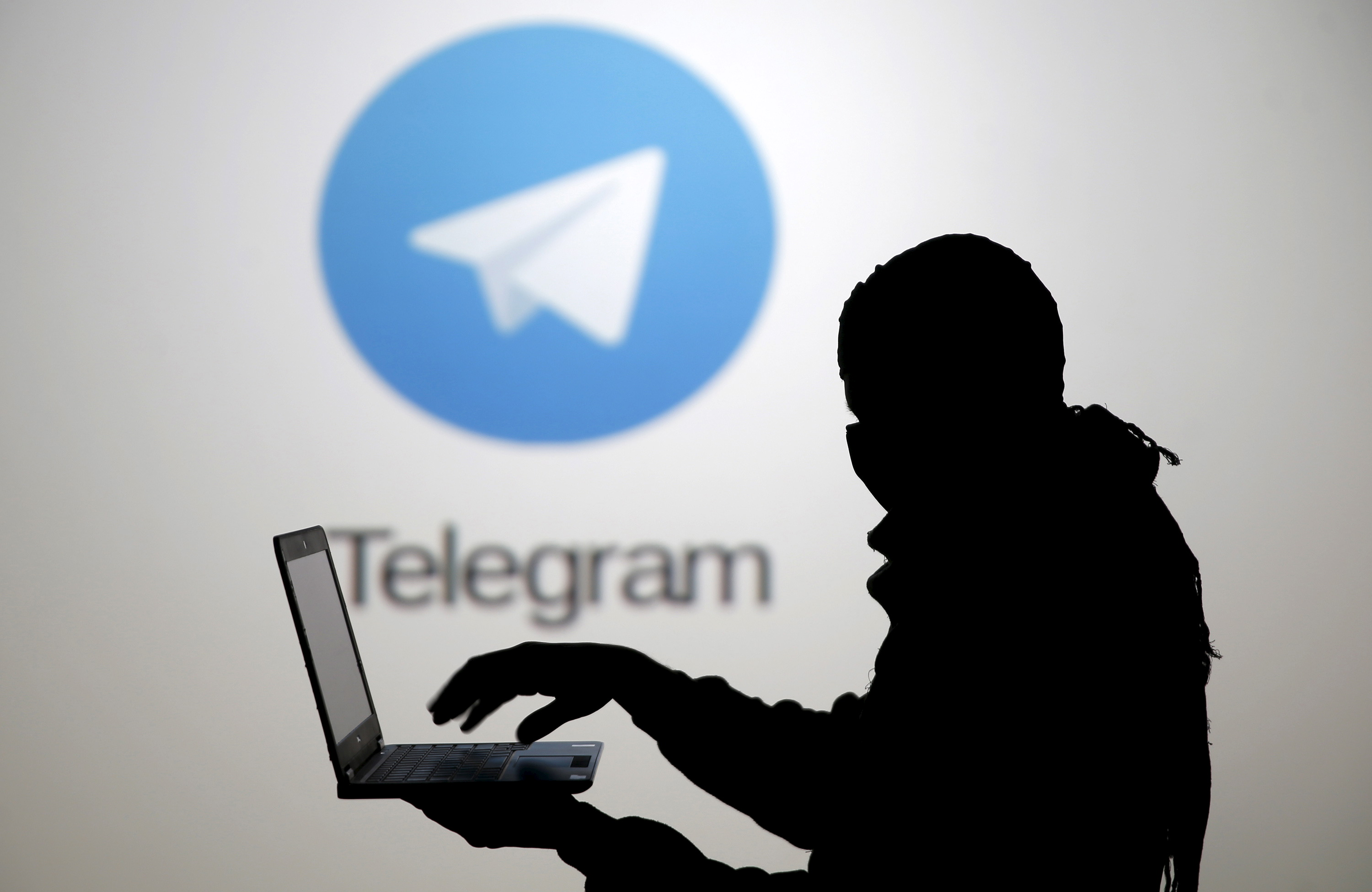A man poses with a laptop in front of a screen showing the Telegram logo in this picture illustration taken in Zenica, Bosnia and Herzegovina November 18, 2015. The mobile messaging service Telegram, created by the exiled founder of Russia's most popular social network site, has emerged as an important new promotional and recruitment platform for Islamic State. The service, set up two years ago, has caught on in many corners of the globe as an ultra-secure way to quickly upload and share videos, texts and voice messages. It counts 60 million active users around the world. Picture taken November 18. REUTERS/Dado Ruvic - RTS7W3P